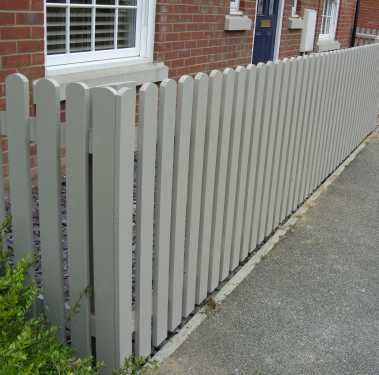 Palisade fencing with round tops in muted clay