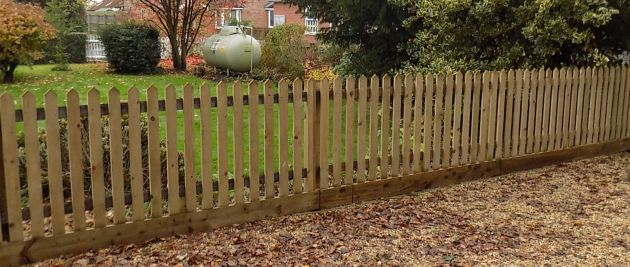 Palisade with pointed tops and gravel boards