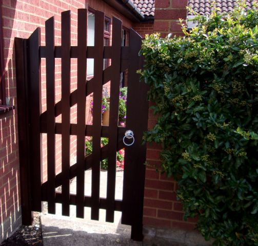Helmingham pedestrian gate with round top and flat pales with a wider spacing in Sadolin Rosewood