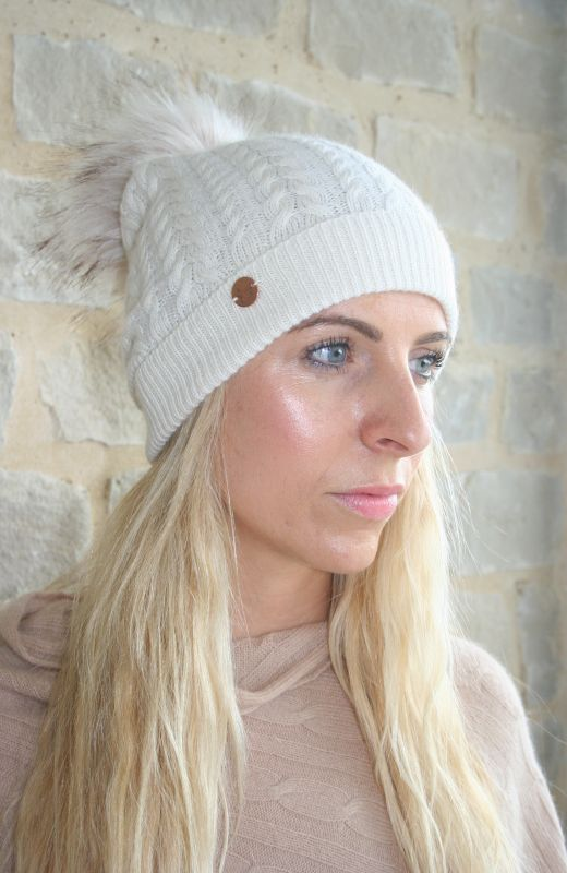 Cable knit beanie with faux fur detachable pom in cream.