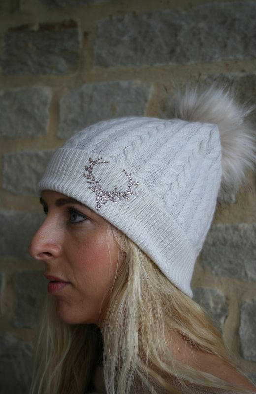 Cable beanie with 5cm diamante stag embellishment and detachable faux fur pom in cream.